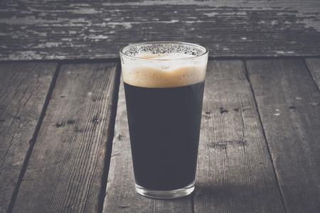 cerveza negra: Pinta de cerveza oscura sobre fondo de madera con estilo de película de la vendimia