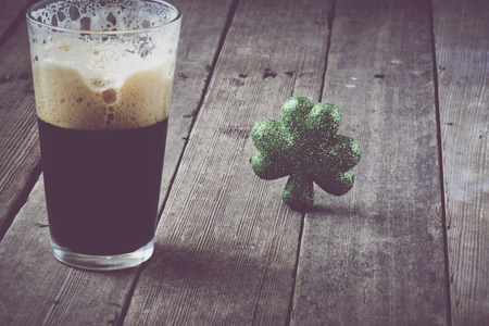 stout: Pint of Stout Beer with Green Shamrock with Vintage Film Filter