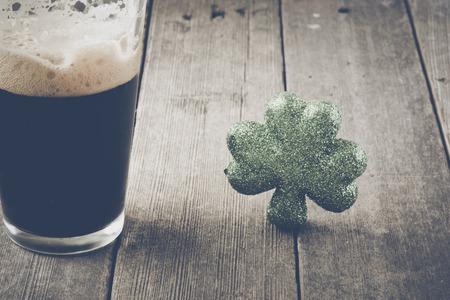 cerveza negra: Pinta de cerveza de malta de cerveza con el trébol verde con filtro de película de la vendimia Foto de archivo