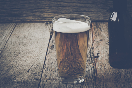 pilsner: Pint of Pilsner Beer on Wood Background with Vintage Instagram Film Style Stock Photo