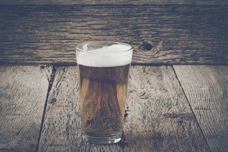 pilsner beer glass: Pint of Pilsner Beer on Wood Background with Vintage Instagram Film Style Stock Photo