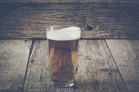 pilsner: Pinta de cerveza Pilsner sobre fondo de madera con vintage Instagram Cine Estilo Foto de archivo