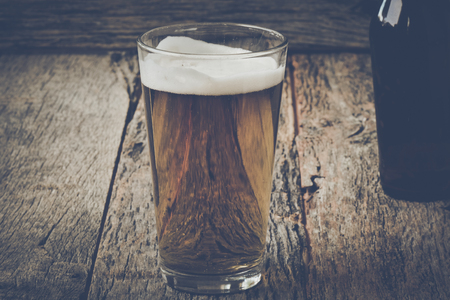 pilsner: Pint of Pilsner Beer on Wood Background with Vintage Film Style