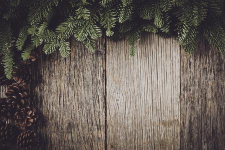 ramo di un albero su fondo in legno rustico con pigne Archivio Fotografico