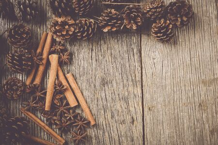 Cinnamon sticks, star anise and pine cones on rustic wood background