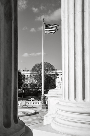 Flag flying between two pillars of the Supreme Court of the United States