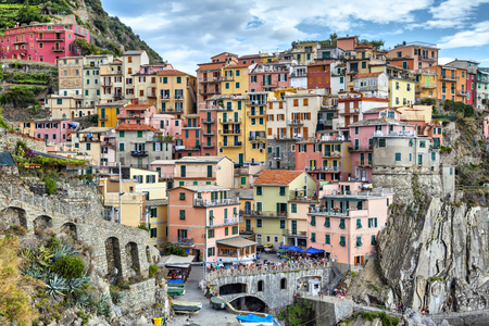 chaotically: Narrow and colorful, chaotically standing houses on a cliff above the sea at summer day in Manarola, Italy