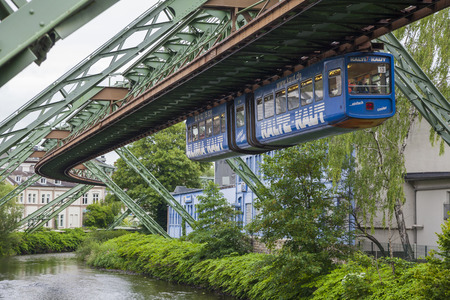 echnology: Wuppertal, Germany - July 05 2014: Blue wagon of Wuppertal Suspension Railway going above the river Wupper