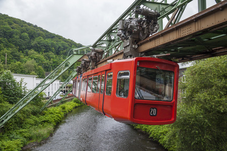 Red wagon of Wuppertal Suspension Railway going above the river Wupper