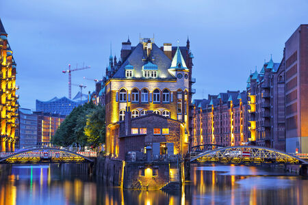 House and two brides illuminated at evening in old warehouse district (Speicherstadt), Hamburg, Germany photo