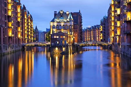 家と古い倉庫街 (シュパイヘーシュタット)、ハンブルク、ドイツの夜照らされた 2 つの花嫁 写真素材
