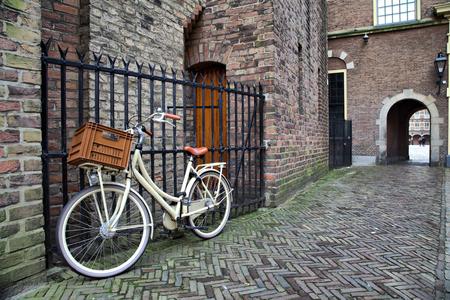 White bicycle near the lattice in Binnenhof, Hague, Netherlands