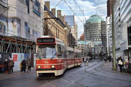 htm: Hague, Netherlands ? February 03, 2014: Old red tram rides on Kalvermarkt street in Hague