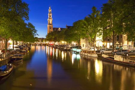 westerkerk: Western church reflecting in water of Prinsengracht canal in Amsterdam