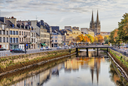 Embankment of river Odet and cathedral of Saint-Corentin reflecting in river, Quimper, Brittany, France