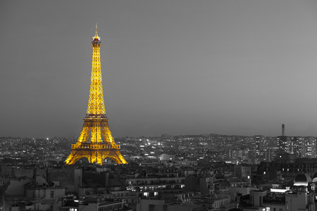 illuminated: Paris, France - October 18 2014: Aerial view on illuminated Eiffel Tower with city on background, black and white effect applied