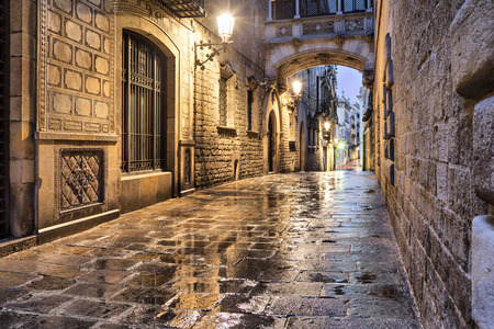 ancient buildings: Narrow street Carrer del Bisbe in gothic quarter, Barcelona, Spain
