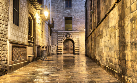 Wet, narrow and dark street in gothic quarter, Barcelona, Spain