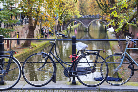 Black bicycle tied to the fence of the bridge across the canal in Utrecht, Netherlands