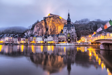Church and Citadel reflecting in river Meuse in the foggy winter evening, Dinant, Wallonia, Belgium