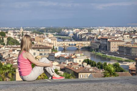 Blonde girl in a pink T-shirt is sitting on a background of the Ponte Vecchio bridge in Florence, Italy