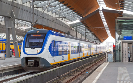 railway transportation: Amsterdam, Netherlands - June 23, 2014: White-blue shuttle train stays on Amsterdam Arena rail station Editorial
