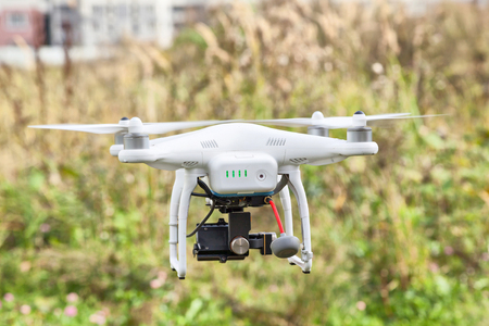 remote controlled: White remote controlled drone in flight with clover-leaf antenna and 3d gimbal