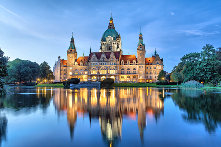 New City Hall of Hannover reflecting in water in the evening, Lower Saxony, Germany