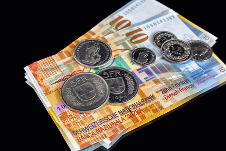 swiss franc note: Swiss Franks - a few banknotes and coins of different value isolated on black background