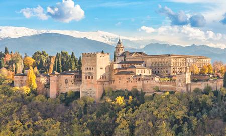 アルハンブラ宮殿 - 背景、グラナダ、アンダルシア、スペインの雪山と黄色の秋の木々 に囲まれた中世のムーア人の要塞