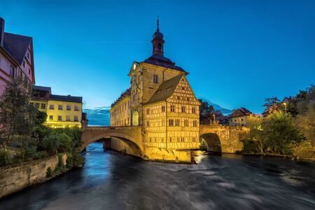 Bamberg. Illuminated building of Old Town Hall of Bamberg (Altes Rathaus) with two bridges over the Regnitz river in the evening, Germany