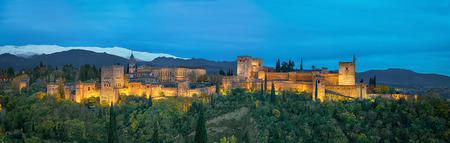 Panorama of Alhambra - medieval Moorish fortress surrounded by yellow autumn trees illuminated in the evening, Granada, Andalusia, Spain Standard-Bild
