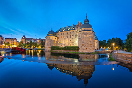 Medieval Orebro Castle reflecting in water in the evening, Orebro, Sweden