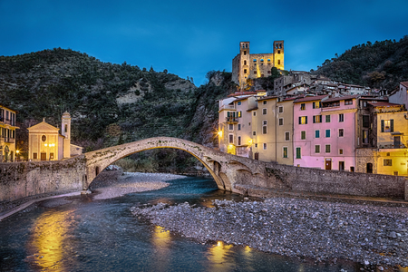 Dolceacqua town at dusk, Liguria, Italy, 15th century Romanesque bridge (Ponte Vecchio), over the Nervia creek, colorful houses and ruins of the 13th century castle