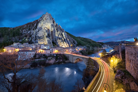 Sisteron in the evening: The Rocher de la Baume - peculiar shaped rock and bridge over Durance river, Alpes-de-Haute-Provence, France Imagens - 95124347
