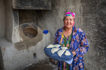 Bukhara, Uzbekistan - April 20 2018: An elderly woman is preparing to put the samsa in to the tandoor - a traditional Uzbek oven