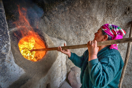 Bukhara, Uzbekistan - April 20 2018: An elderly woman is kindling a tandoor - a traditional Uzbek oven used in cooking and baking flatbread