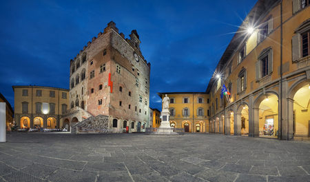 Prato, Italy. Panorama of Piazza del Comune square with historic building of medieval Town Hall at dusk
