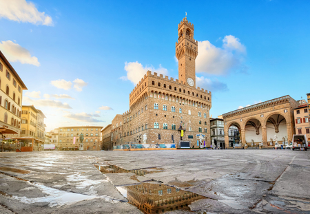 Florence, Italy. View of Piazza della Signoria square with Palazzo Vecchio reflecting in a puddle at sunrise