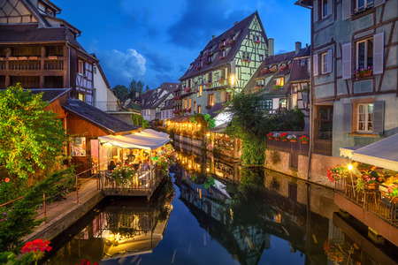 Colmar, France. Half-timbered houses and verandas of restaurants reflecting in the water at dusk in Petite Venise area Stock Photo