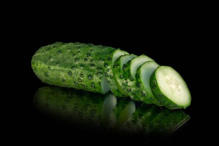 Green cucumber (gherkin) partly sliced rings on a black background