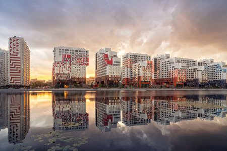 Moscow, Russia. View of new modern residential buildings reflecting in water on sunset in Nagatinsky Zaton district