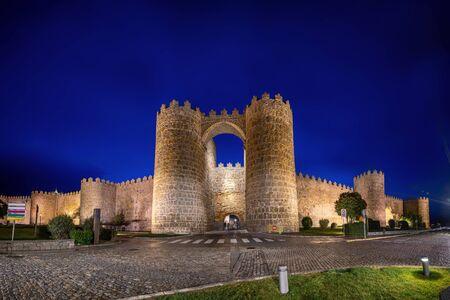 Avila, Spain. View of historic city gate Puerta de San Vicente at dusk Stock Photo