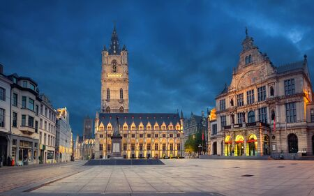 Ghent, Belgium. Sint-Baafsplein square at dusk with building of historic Town Hall and famous Belfry of Ghent