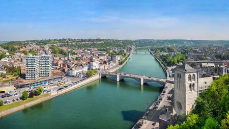 Huy, Wallonia, Belgium. Panoramic aerial cityscape with Meuse river, bridge and historic church Standard-Bild