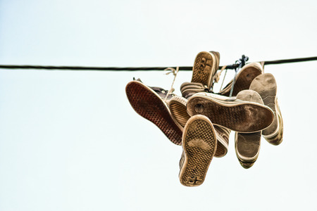 poorness: Old shoes thrown over black cable Stock Photo