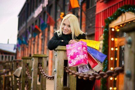 tasking: Lovely smiling blond girl with shopping bags Stock Photo