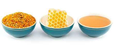 Honey, honeycomb and pollen granules in green porcelain bowls in a row, on white isolated background photo