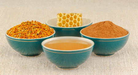 antiviral: Honey, honeycomb, pollen granules and cinnamon in green porcelain bowls, on rustic table cloth