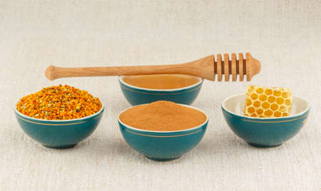 Pollen granules, honeycomb, honey and cinnamon in green porcelain bowls with wooden dipper, on rustic table cloth photo